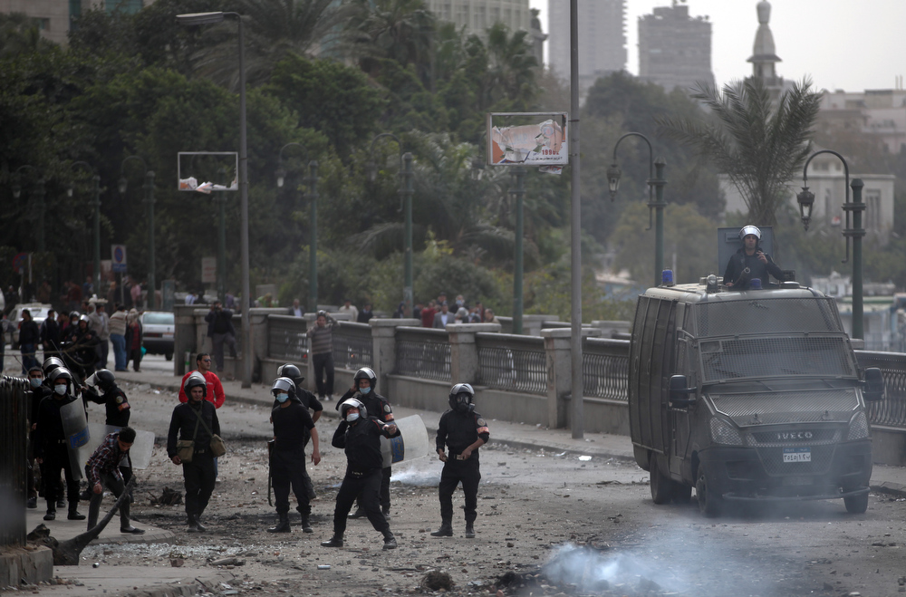 . Egyptian riot police clash with protesters, not seen, near Tahrir Square, Cairo, Egypt, Monday, Jan. 28, 2013. Health and security officials say a protester has been killed in clashes between rock-throwing demonstrators and police near Tahrir Square in central Cairo. The officials say the protester died Monday on the way to the hospital after being shot. (AP Photo/Khalil Hamra)
