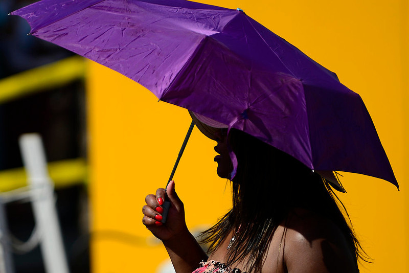 . Lesley Brown, 38, of Aurora, uses her umbrella to shade from the sun as she walks through the Five Points Jazz Festival. The festival runs 11am to 8pm on May 18, 2013 and is a free community event highlighting local musicians, art and the historic Denver Five Points neighborhood.  (Photo By Mahala Gaylord/The Denver Post)