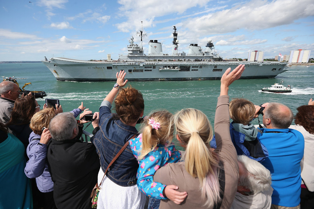 """. Relatives of navy personnel wave as the helicopter carrier HMS Illustrious departs Portsmouth for a deployment to the Mediterranean on August 12, 2013 in Portsmouth, England. Three Royal Navy warships have set sail for the Mediterranean for a routine deployment amid increased tensions between Britain and Spain over the sovereignty of Gibraltar. The Ministry of Defense has described the warship\'s movements as \""""long-planned\"""" and part of \""""a range of regular and routine deployments\"""".  (Photo by Oli Scarff/Getty Images)"""