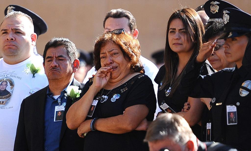 . Family members look on as pallbearers carry the casket of LAPD Officer Roberto Sanchez during his funeral at the Cathedral of Our Lady of the Angels in Los Angeles, CA May 14, 2014.  Sanchez was killed in a hit-and-run crash involving a SUV driver who is accused of deliberately ramming the officer\'s patrol car in Harbor City.(Andy Holzman/LA Daily News)