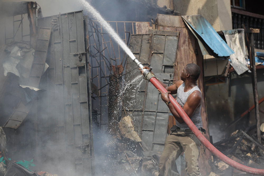 Description of . A firefighter  tries to contain fire at a burnt out warehouse on Lagos Island in Lagos, Nigeria, Wednesday, Dec. 26, 2012. An explosion ripped through a warehouse Wednesday where witnesses say fireworks were stored in Nigeria's largest city, sparking a fire. It wasn't immediately clear if anyone was injured in the blast that firefighters and locals struggled to contain. (AP Photos/Sunday Alamba)