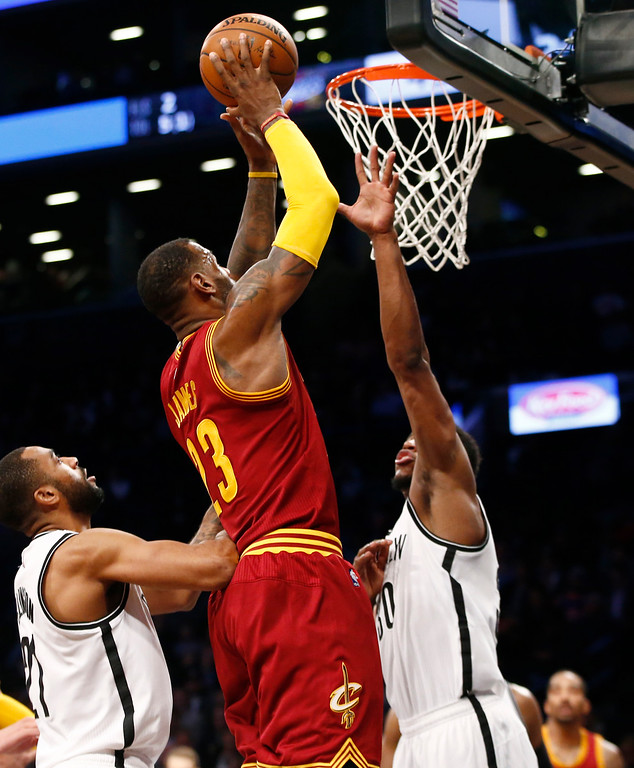 . Cleveland Cavaliers forward LeBron James (23) shoots over the defense of Brooklyn Nets guard Wayne Ellington (21) and Nets forward Thaddeus Young (30) in the first half of an NBA basketball game, Wednesday, Jan. 20, 2016, in New York. (AP Photo/Kathy Willens)