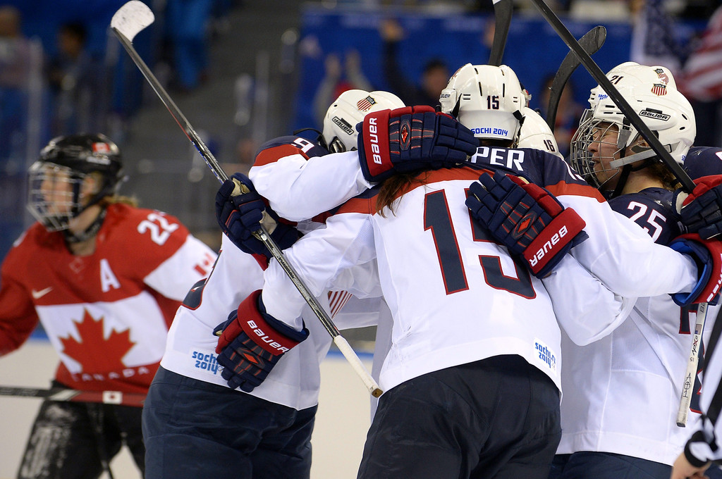 . US players celebrate after US Hilary Knight scored their team\'s first goal during the Women\'s Ice Hockey Group A match between Canada and USA at the Sochi Winter Olympics on February 12, 2014 at the Shayba Arena. AFP PHOTO / ALEXANDER NEMENOV/AFP/Getty Images