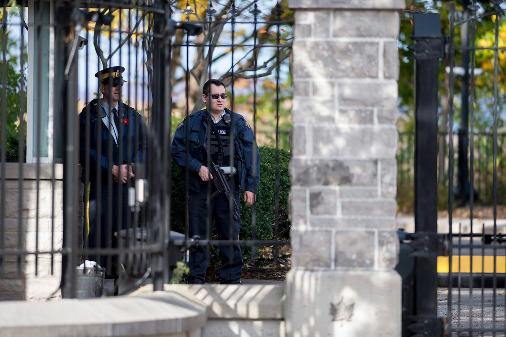 . A heavily armed Royal Canadian Mounted Police officer stands guard at 24 Sussex, the residence of Canada\'s Prime Minister Stephen Harper after a reported shooting at Parliament building in Ottawa on Wednesday, Oct. 22, 2014.  A soldier standing guard at the National War Memorial has been shot by an unknown gunman and there have been reports of gunfire inside the halls of Parliament. (AP Photo/The Canadian Press, Justin Tang)