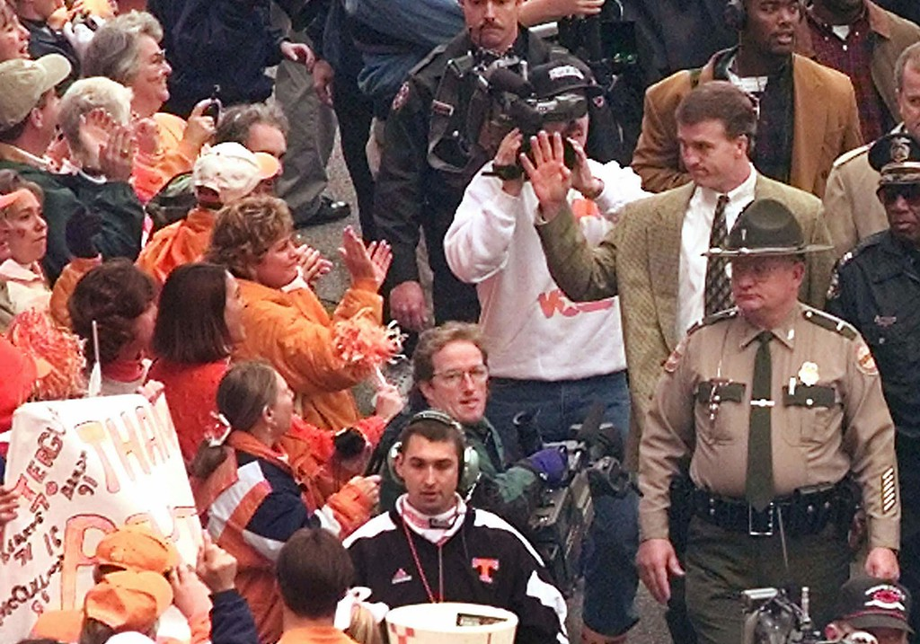 . Tennessee quarterback Peyton Manning, right, waves to the crowd as he leads the team on their traditional walk to the stadium to play Vanderbilt in their final regular-season game on Saturday, Nov. 29, 1997, in Knoxville, Tenn. It will be Manning\'s last home game. (AP Photo/Mark Humphrey)