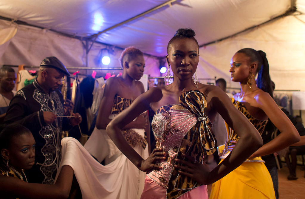 . Models wear creations by Habib Sangare, back left, of Ivory Coast, backstage at Hotel des Almadies, in Dakar, Senegal, Saturday, June 22, 2013. After a Friday show held in a dusty marketplace in the working class suburb of Guediawaye, the runway finale of Dakar Fashion Week was held at a luxury hotel and showcased the work of 14 designers from West Africa, Europe, South America, and the Caribbean. (AP Photo/Rebecca Blackwell)