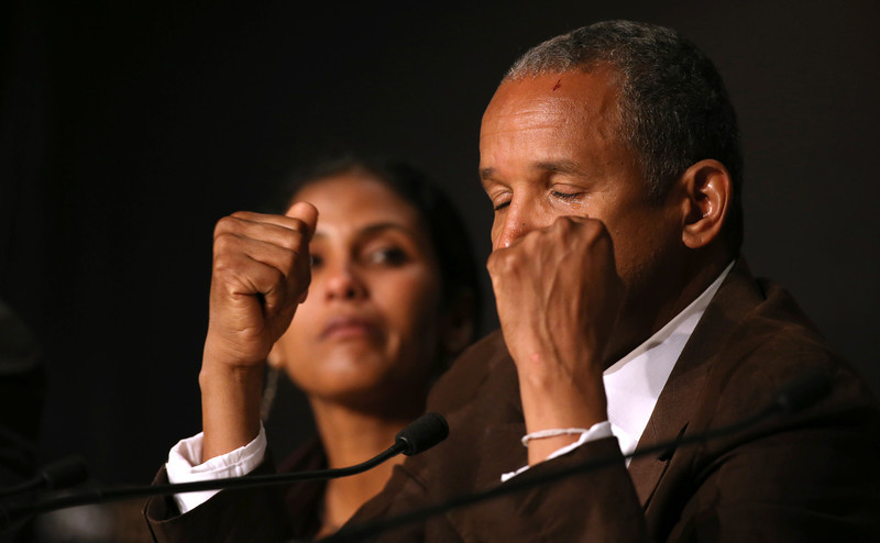 . Director Abderrahmane Sissako cries while answering a question during a press conference for Timbuktu at the 67th international film festival, Cannes, southern France, Thursday, May 15, 2014. (AP Photo/Alastair Grant)
