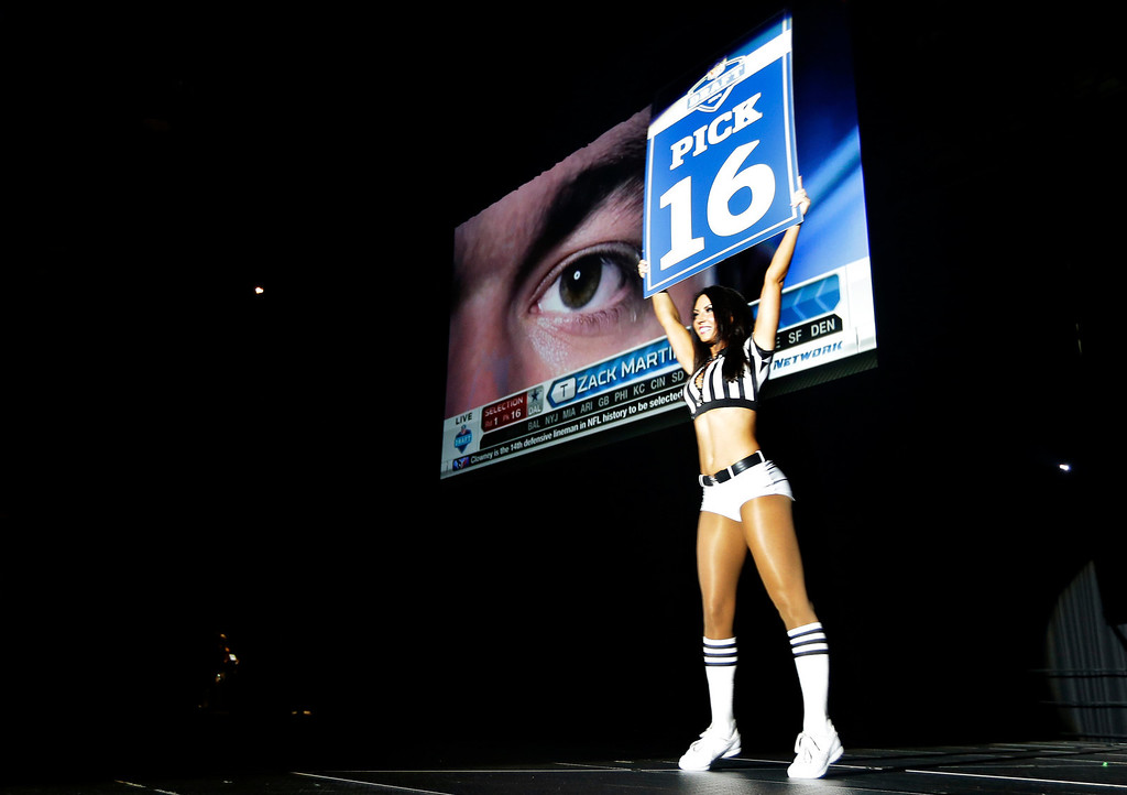 . A Seattle Seahawks Sea Gals cheerleader carries a sign to announce the 16th pick in the first round of the NFL football draft, the selection of Notre Dame offensive tackle Zack Martin by the Dallas Cowboys, Thursday, May 8, 2014 during the Seahawks draft party at the CenturyLink Field Events Center in Seattle. (AP Photo/Ted S. Warren)