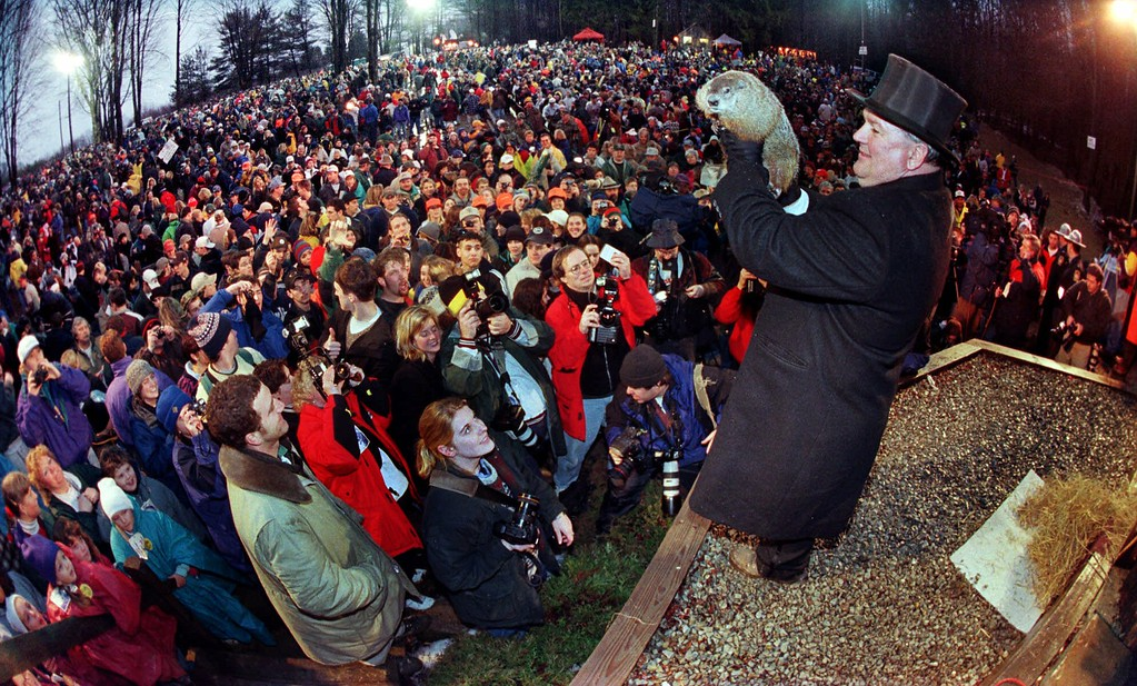 . Handler Bill Deeley holds Punxsutawney Phil, who greets visitors to his burrow on Gobblers Knob in Punxsutawney, Pa., at sunrise Tuesday, Feb. 2, 1999. The weather prognositcating groundhog did not see his shadow, and predicted an early spring. (AP Photo/Gene J. Puskar)