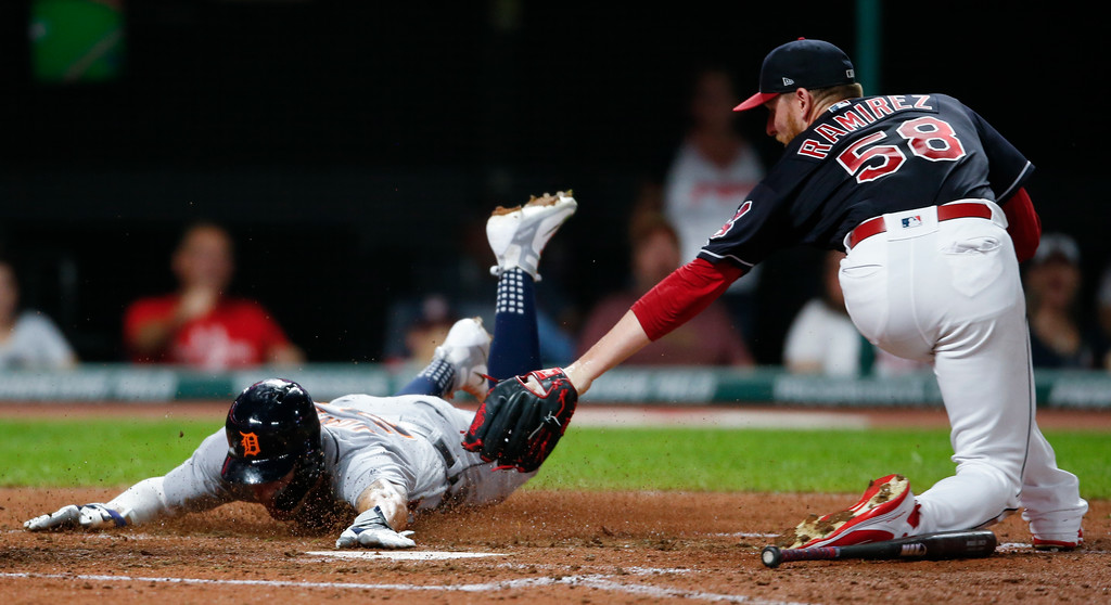 . Detroit Tigers\' JaCoby Jones, left, scores past Cleveland Indians\' Neil Ramirez after a wild pitch by Ramirez during the eighth inning of a baseball game, Friday, Sept. 14, 2018, in Cleveland. (AP Photo/Ron Schwane)