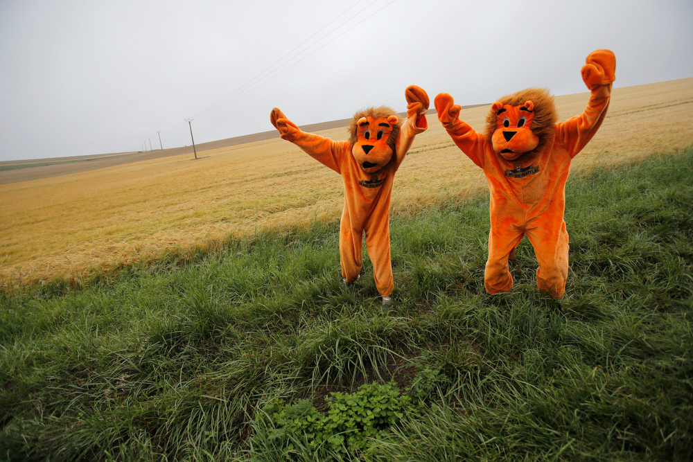 . Two cycling fans in disguise wait for the pack to pass during the sixth stage of the Tour de France cycling race over 194 kilometers (120.5 miles) with start in Arras and finish in Reims, France, Thursday, July 10, 2014. (AP Photo/Christophe Ena)