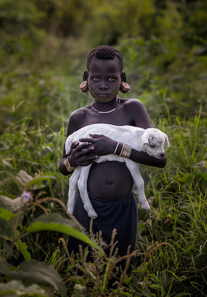 A young Murci girl holding a goat. She is wearing big traditional earrings but the lip plate has not been an option for her. Although many women still wear the lip plate more and more young girls are opting out.  Southern Ethiopia, 2017.