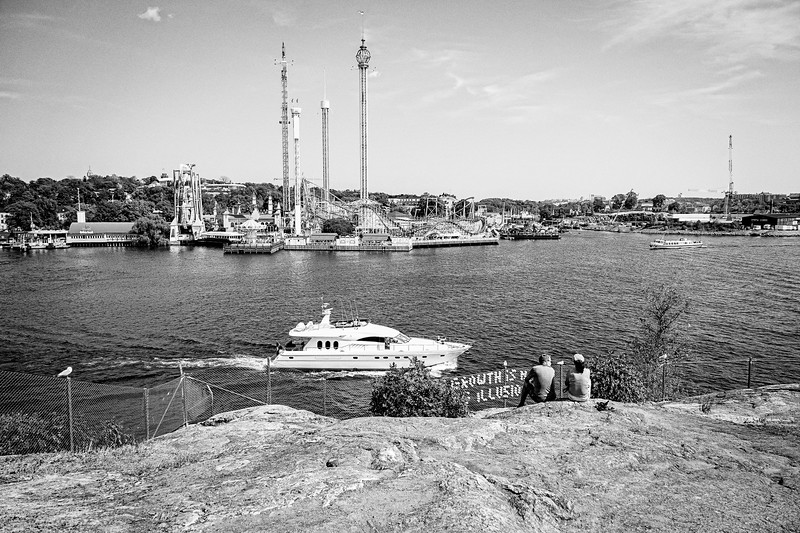 A couple chats and watches boats pass by in front of Gröna Lund, amusement park, near Kastellholmen on Stockholm.