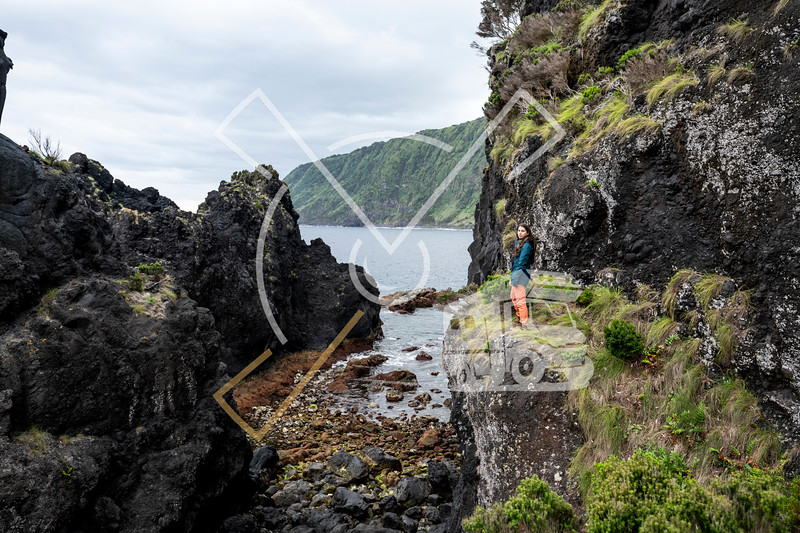 Young woman walking through the lava debris field landscape of Poça Simão Dias, near the natural pools of Fajã do Ouvidor at the north coast of the Sao Jorge Island in the Azores