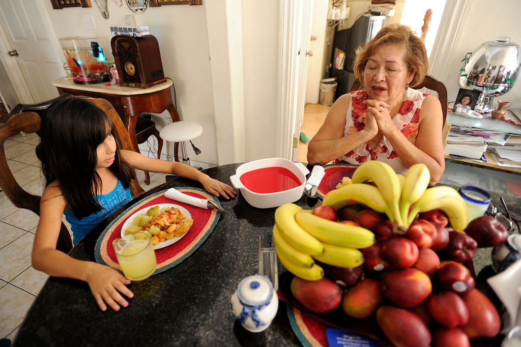 . Saying grace before having dinner, Juanita Chavez, 69, of Los Angeles has raised her great-grandaughter Victoria Licea,7,since she was 1-month old. Chavez, who still has a home mortgage, works part-time giving manicures and pedicures at clients\' homes and struggles to make ends meet. Chavez is also taking care of her own daughter, who recently had a heart attack. A recent report by the UCLA Center for Health Policy Research has found that about 40 percent of older grandparents who are responsible for their grandchildren in the state do not have enough income to make ends meet.Los Angeles, CA. 7/11/2013(John McCoy/LA Daily News)