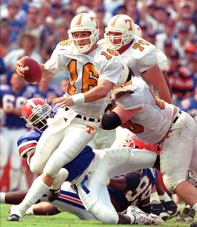 . ]Tennessee quarterback Peyton Manning (16) scrambles away from Florida\'s Thaddeus Bullard (11) during the first quarter Saturday afternoon, Sept. 20, 1997 in Gainesville. (AP Photo/Chris O\'Meara)