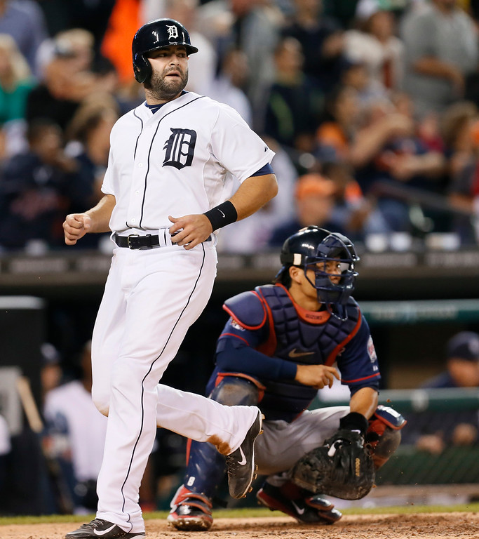 . Detroit Tigers\' Alex Avila, left, scores on a Rajai Davis double as Minnesota Twins catcher Kurt Suzuki, right, looks on in the the seventh inning of a baseball game in Detroit, Thursday, Sept. 25, 2014. (AP Photo/Paul Sancya)