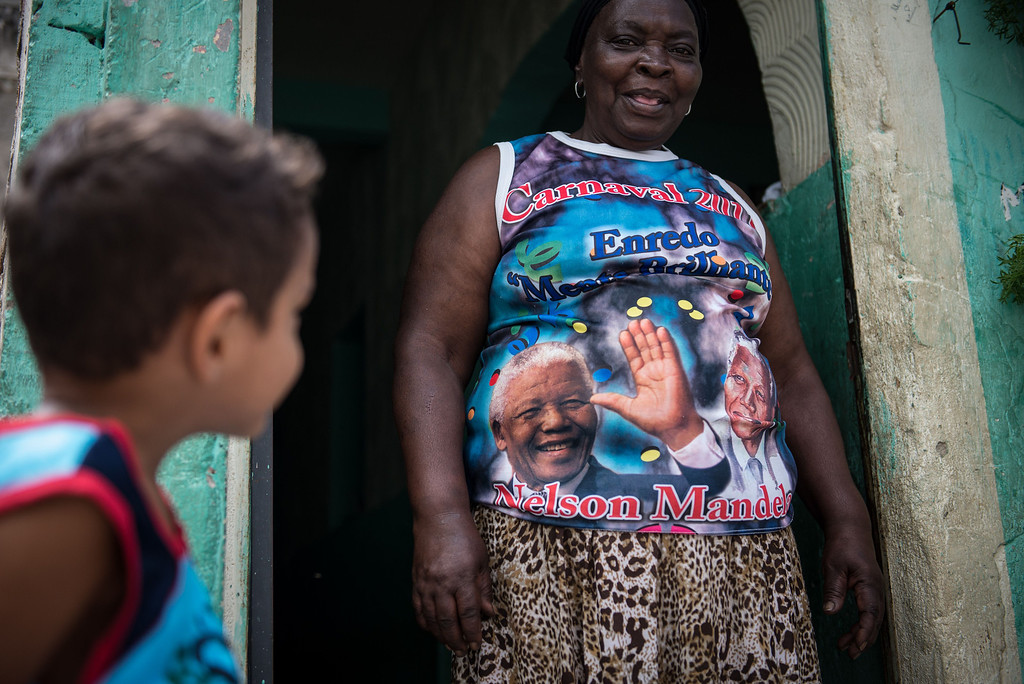 """. Denaide Alves da Fonseca wears a shirt of her carnival drum group \""""Batuqueiros do Mandela\"""" at Mandela shantytown (favela) in Rio de Janeiro, Brazil, on December 6, 2013. The shantytown was named after Mandela to commemorate his discharge from prison in 1990. AFP PHOTO / YASUYOSHI CHIBA/AFP/Getty Images"""