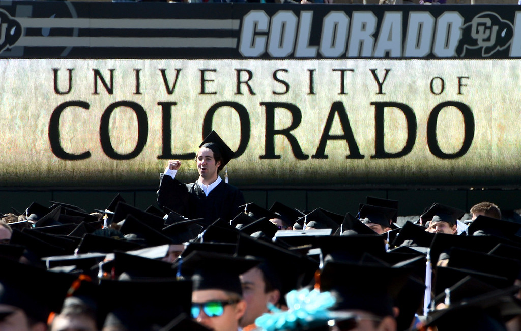 . A University of Colorado student stands up to pump his fist  during the 2013 University of Colorado Spring Commencement on Friday in Boulder, Colorado, May 10, 2013. (AP Photo/The Daily Camera, Cliff Grassmick)