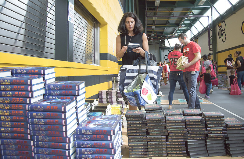 09/04/19  Wesley Bunnell | Staff  Twenty two thousand books were donated to area educators and parents with children by ESPN and Disney on Thursday September 4, 2019 at New Britain Stadium. Jennifer Shannon from Reggio Magnet School of the Arts in Avon looks through the books available.
