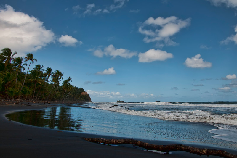 Black sand beach reflecting the sky above.