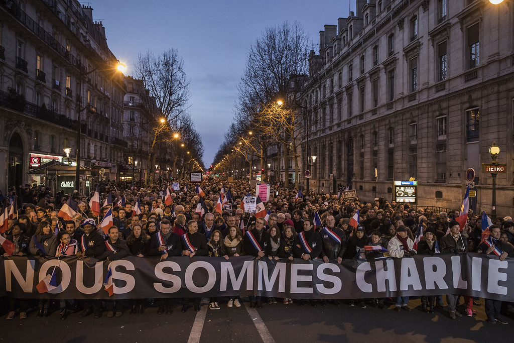 . PARIS, FRANCE - JANUARY 11: Demonstrators make their way along Place de la Republique during a mass unity rally following the recent terrorist attacks on January 11, 2015 in Paris, France. An estimated one million people have converged in central Paris for the Unity March joining in solidarity with the 17 victims of this week\'s terrorist attacks in the country. French President Francois Hollande led the march and was joined by world leaders in a sign of unity. The terrorist atrocities started on Wednesday with the attack on the French satirical magazine Charlie Hebdo, killing 12, and ended on Friday with sieges at a printing company in Dammartin en Goele and a Kosher supermarket in Paris with four hostages and three suspects being killed. A fourth suspect, Hayat Boumeddiene, 26, escaped and is wanted in connection with the murder of a policewoman.  (Photo by Dan Kitwood/Getty Images)