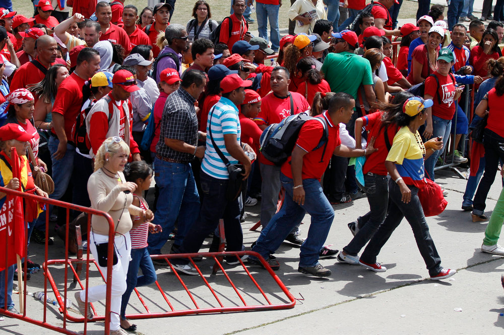. Mourners walk over a barrier outside the military academy where Venezuela\'s late President Hugo Chavez\'s body lies in state at the military academy in Caracas, Venezuela, Thursday, March 7, 2013. While Venezuela remains deeply divided over the country\'s future, the multitudes who reached the president\'s coffin early Thursday were united in grief and admiration for a man many considered a father figure. (AP Photo/Ariana Cubillos)