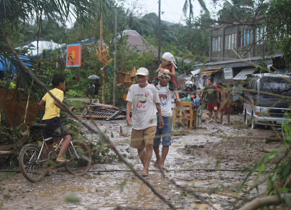 Description of . Residents walk back to their homes after Typhoon Bopha made landfall in Compostela Valley in southeastern Philippines Tuesday Dec. 4, 2012.  Typhoon Bopha (local name Pablo), one of the strongest typhoons to hit the Philippines this year, barreled across the country\'s south on Tuesday, killing at least 40 people and forcing more than 50,000 to flee from inundated villages.  (AP Photo/Karlos Manlupig)