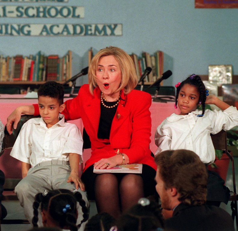 . First lady Hillary Rodham Clinton reacts to a Cleveland Tri-School Learning Academy student Friday, Feb. 14, 1997, in Washington, while sitting with students Myesha Lowe, right, and Paul Ragan.  Clinton and retired Gen. Julius Becton, CEO of DC public schools, discussed Black History Month during their visit to the school.  (AP Photo/Karin Cooper)