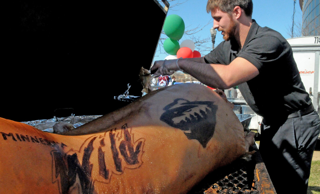 . Zach Enrico of Divine Swine Catering works on the pulled pork as a 177-pound pig with a Minnesota Wild stamp sits atop his grill outside Xcel Energy Center during a pre-game block party.  (Pioneer Press: Sherri LaRose-Chiglo)