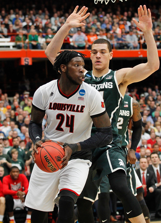 . Louisville\'s Montrezl Harrell (24) looks to pass away from Michigan State\'s Gavin Schilling during the second half of a regional final in the NCAA men\'s college basketball tournament Sunday, March 29, 2015, in Syracuse, N.Y. (AP Photo/Nick Lisi)