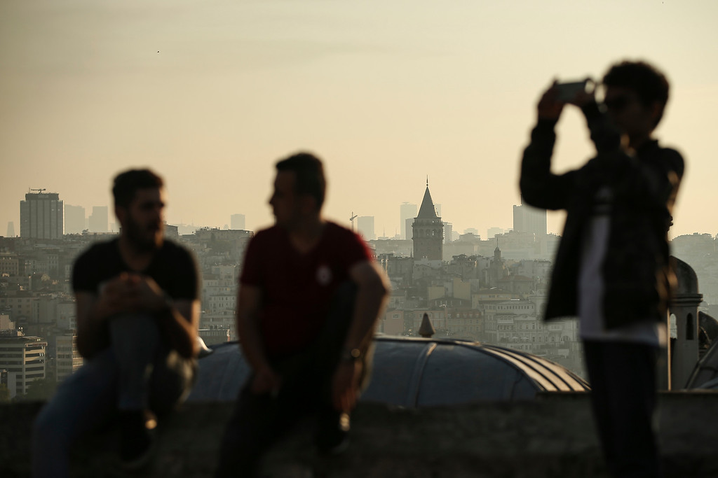 . Backdropped by Istanbul\'s iconic Galata Tower, people enjoy the first day of Eid al-Fitr, which marks the end of the holy fasting month of Ramadan, early Friday, June 15, 2018. (AP Photo/Emrah Gurel)