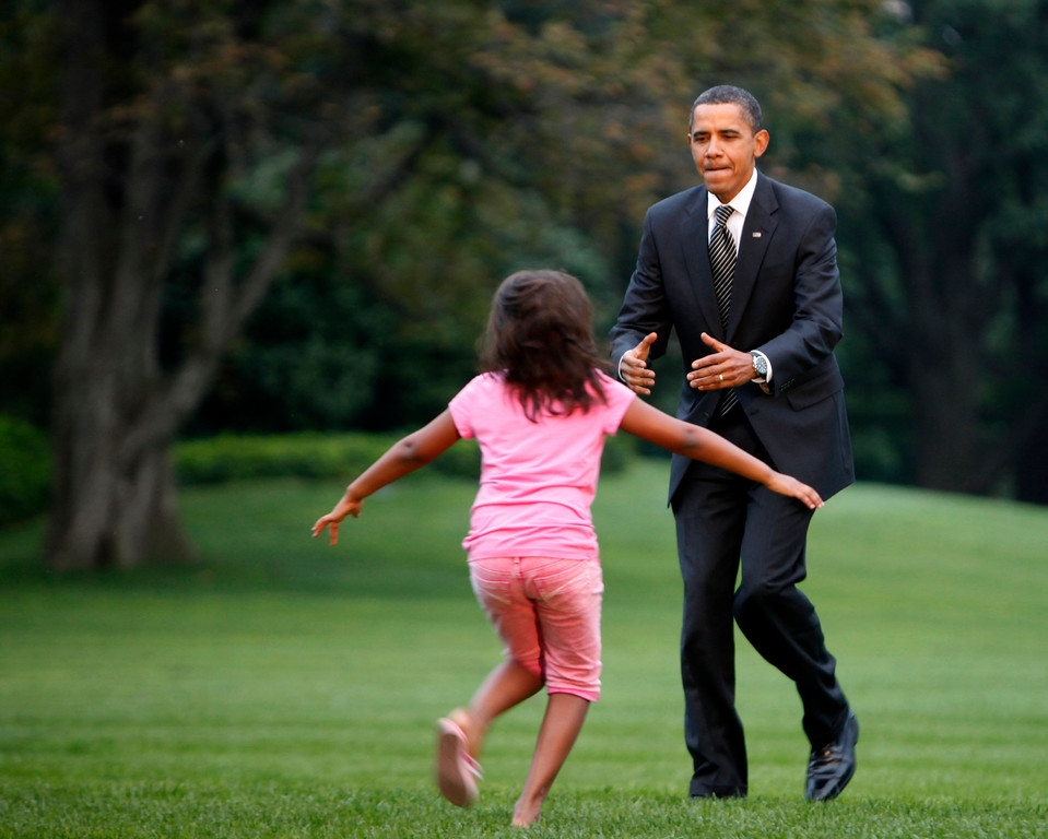 . Sasha Obama, daughter of President Barack Obama, runs from the South Portico of the White House to greet him as he arrives on the South Lawn of the White House in Washington, Tuesday, Sept. 15, 2009. (AP Photo/Gerald Herbert)