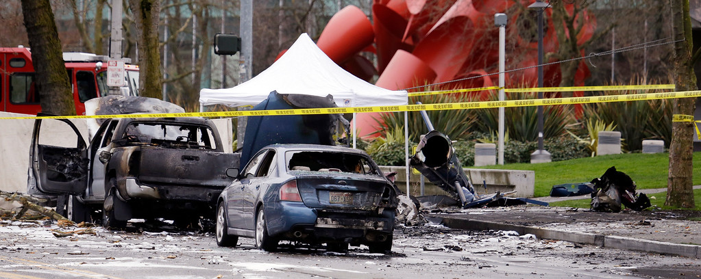 . Caution tape surrounds the charred wreckage of a news helicopter and two vehicles after the chopper crashed into a city street near the Space Needle, Tuesday, March 18, 2014, in Seattle. Two people were killed and another was critically injured, according to the Seattle Fire Department. (AP Photo/Elaine Thompson)