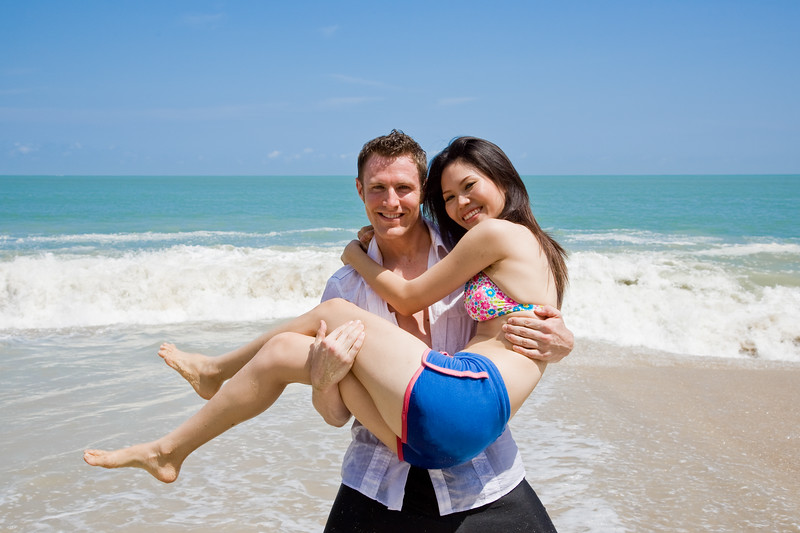 hunky caucasian man carrying gorgeos girl on the beach