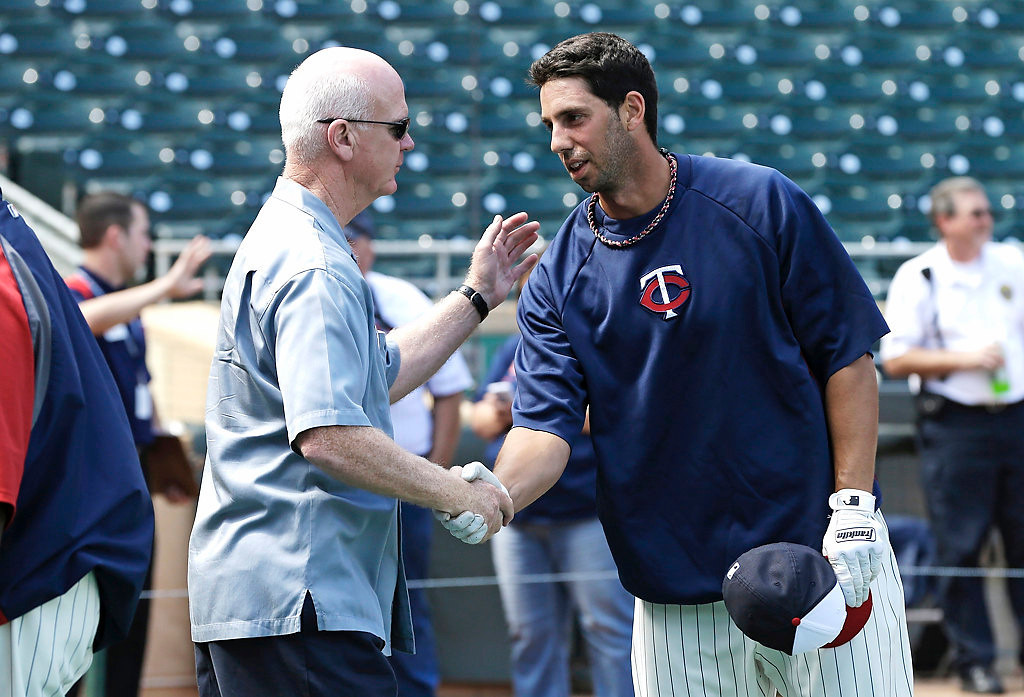 . Minnesota Twins executive vice president and general manager Terry Ryan, left, greets designated hitter Chris Colabello during warmups. (AP Photo/Jim Mone)