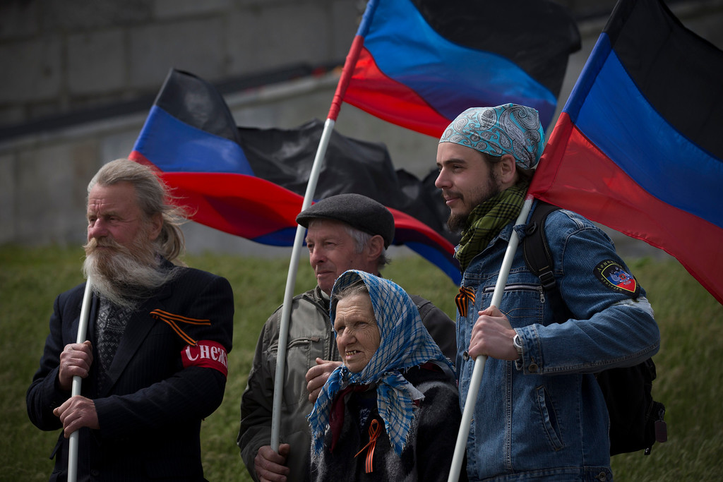. Pro-Russian activists hold Donetsk republic flag during celebrations of the Victory Day at a WWII memorial in Saur-Mogila, about 60 km. (31 miles) east of Donetsk, Ukraine, Friday, May 9, 2014. Russia wants Ukraine to adopt a new constitution that would give broad powers to its regions and would also help Moscow keep the country\'s east in its orbit. It also has sought guarantees that Ukraine would not join NATO. (AP Photo / Alexander Zemlianichenko)