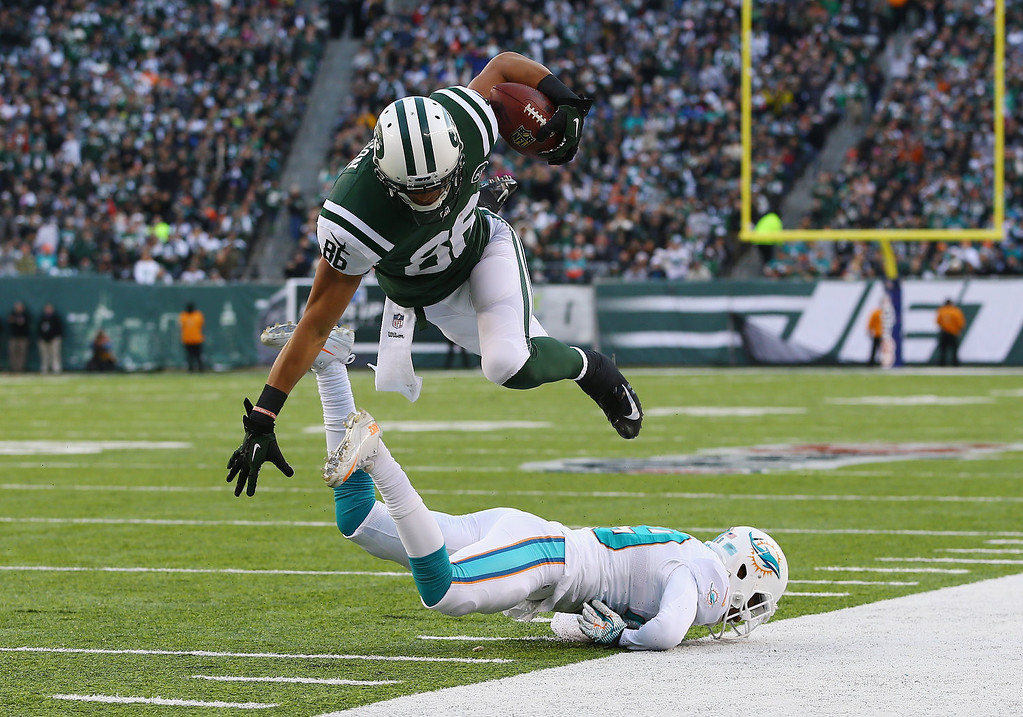 . David Nelson #86 of the New York Jets leaps for a gain after a catch as  Jimmy Wilson #27 of the Miami Dolphins makes the tackle during their game at MetLife Stadium on December 1, 2013 in East Rutherford, New Jersey.  (Photo by Al Bello/Getty Images)