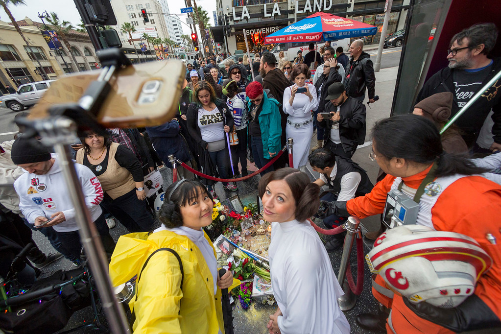 ". Costumed fans dressed as Princess Leia, in honor of actress Carrie Fisher, who played Leia in the ""Star Wars\"" movie series, gather to take photographs at an impromptu memorial for Fisher created on a blank Hollywood Walk of Fame star in the Hollywood section of Los Angeles, Saturday, Dec. 31, 2016. Fisher had been hospitalized Dec. 23 after falling ill aboard a flight and was treated by paramedics at the Los Angeles airport. One day after Fisher\'s death on Dec. 27, her mother actress, 84-year-old Debbie Reynolds, died as well. (AP Photo/Damian Dovarganes)"