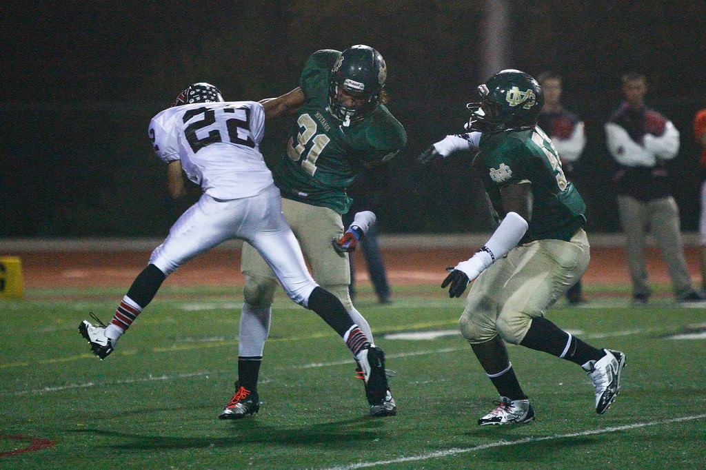 . Stanton Gilbertson #22 of Palos Verdes is tackled by Jahlani Tavai #31 and Khalil Sonko #51 of Mira Costa during a Bay League matchup at Mira Costa High School on Friday, October 18, 2013 in Manhattan Beach, Calif.  (Michael Yanow / For the Daily Breeze)