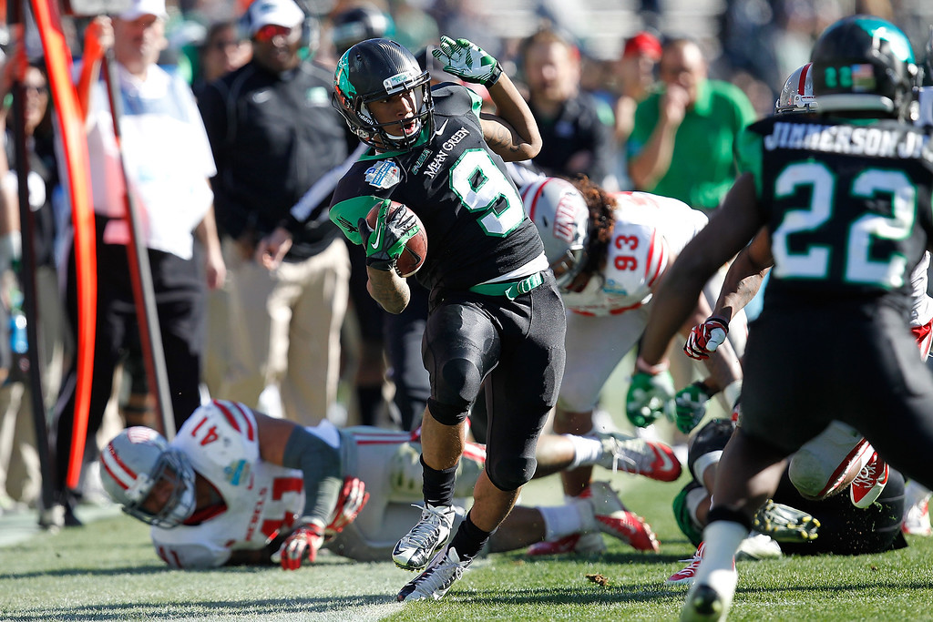 . DALLAS, TX - JANUARY 01: Carlos Harris #9 of the North Texas Mean attempts to stay in bounds against the UNLV Rebels during the Heart of Dallas Bowl at Cotton Bowl Stadium on January 1, 2014 in Dallas, Texas.  (Photo by Sarah Glenn/Getty Images)