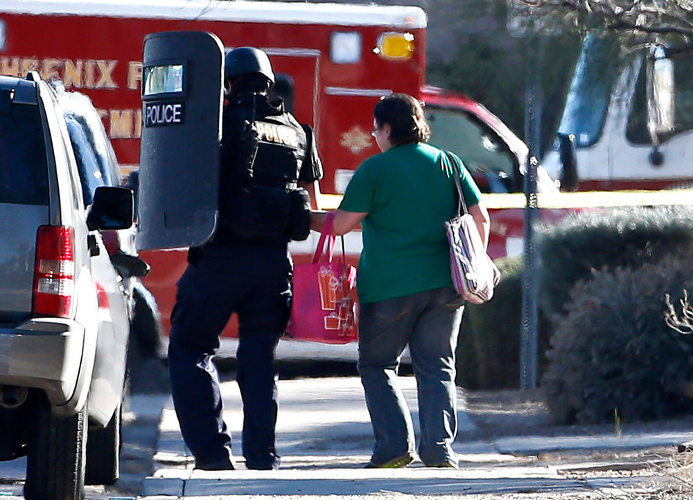 Description of . A member of the Phoenix Police Department SWAT team leads a female neighbor away to safety, as the the SWAT team prepares to enter the home of a suspected gunman who opened fire at a Phoenix office building, wounding three people, one of them critically, and setting off a manhunt that led police to surround his house for several hours before they discovered he wasn't there, Wednesday, Jan. 30, 2013, in Phoenix.  Authorities believe there was only one shooter, but have not identified him or a possible motive for the shooting. They don't believe the midmorning shooting at the complex was a random act. (AP Photo/Ross D. Franklin)