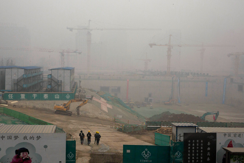 """. Construction workers walk into a work site during a hazy day in Beijing, China, Wednesday, Feb. 26, 2014. Beijing remained cloaked in hazardous white pollution hiding much of its skyline Wednesday, despite the announced closures or production cuts at 147 of the city\'s industrial plants. Chinese characters at bottom left reads \""""China dream, my dream\"""" at right reads \""""China, Go!\"""" (AP Photo/Ng Han Guan)"""