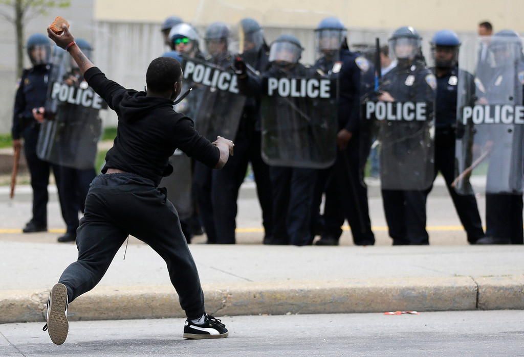 . A man throws a brick at police Monday, April 27, 2015, following the funeral of Freddie Gray in Baltimore. Gray died from spinal injuries about a week after he was arrested and transported in a Baltimore Police Department van. (AP Photo/Patrick Semansky)