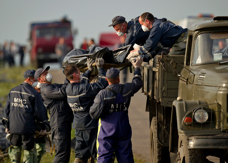 . Emergency workers load the body of a victim on a truck at the crash site of Malaysia Airlines Flight 17 near the village of Hrabove, eastern Ukraine, Saturday, July 19, 2014. World leaders demanded Friday that pro-Russia rebels who control the eastern Ukraine crash site of Malaysia Airlines Flight 17 give immediate, unfettered access to independent investigators to determine who shot down the plane. (AP Photo/Vadim Ghirda)