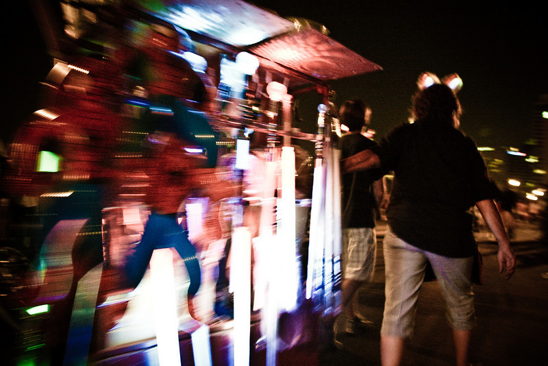 A street vendor pulls her cart lit up with light sabers -  Union St N./Woodland St. bridge, July th 2010.