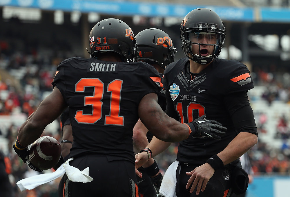 Description of . Jeremy Smith #31 of the Oklahoma State Cowboys celebrates a touchdown with Clint Chelf #10 against the Purdue Boilermakers during the Heart of Dallas Bowl at Cotton Bowl on January 1, 2013 in Dallas, Texas.  (Photo by Ronald Martinez/Getty Images)