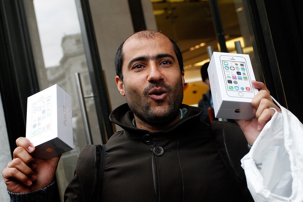 . An ecstatic iPhone fan clutches two new iPhone 5S\'s as he leaves the Apple store with his purchases, on Regent Street on September 20, 2013 in London, England.  (Photo by Mary Turner/Getty Images)