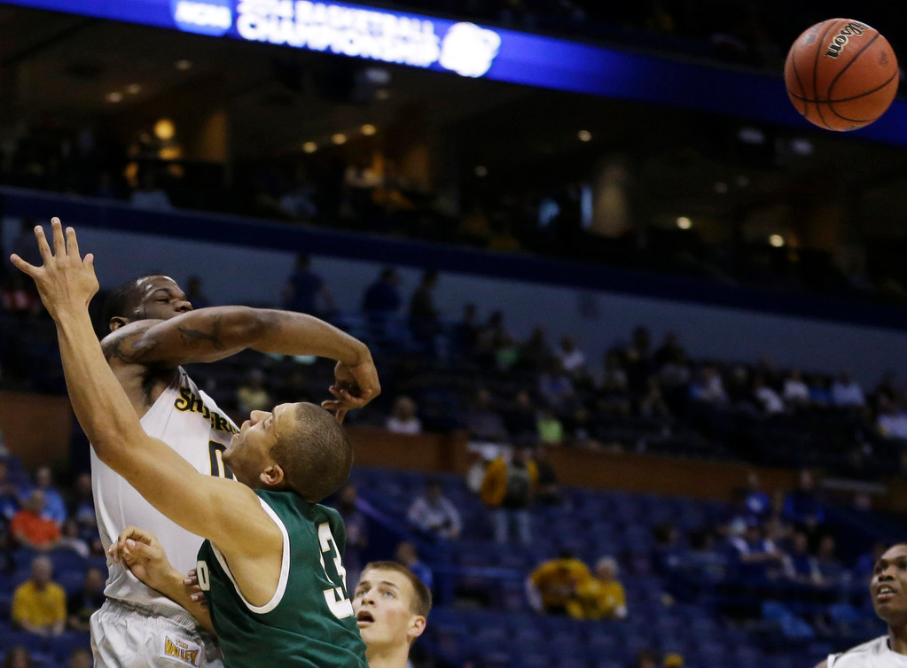 . Wichita State forward Chadrack Lufile (0) blocks a shot by Cal Poly forward Chris Eversley (33) during the first half of a second-round game in the NCAA college basketball tournament Friday, March 21, 2014, in St. Louis. (AP Photo/Jeff Roberson)