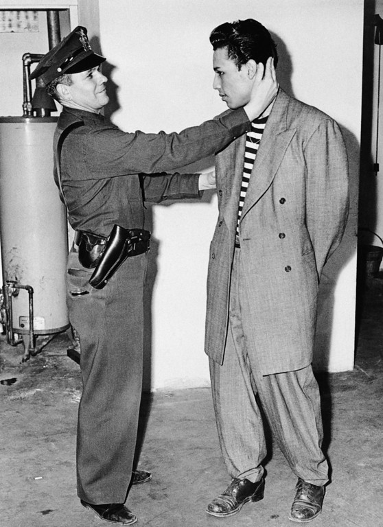 ". Deputy Sheriff Bartley Brown of East Los Angeles inspects the haircut of prisoner Alex ""Largo\"" Rodriguez, who is wearing an $85.00 zoot suit June 7, 1943. (AP Photo)"